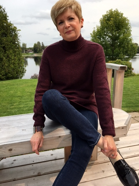 woman in burgundy sweater and jeans sitting on bench, river in background
