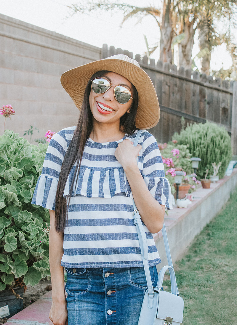 blue striped ruffle blouse with sunglasses and hat head tilt pose