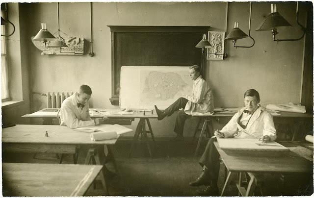 Mustavalkonen kuva, Nuoria miehiä huoneessa, jossa taustalla liitutaulu. Miehillä valkoiset takit päällään.