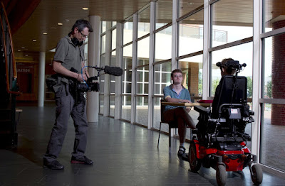 Production photo of David Jame Savarese (Deej), a thin white male  with short, cropped hair and glasses, wearing a light blue polo shirt and beige  slacks, seated at a table facing his girlfriend who is seated in a power chair  back to us, facing  him. A man holding a camera is standing to their left and  caught in the act of filming them. ©DEEJ movie www.deejmovie.com/press