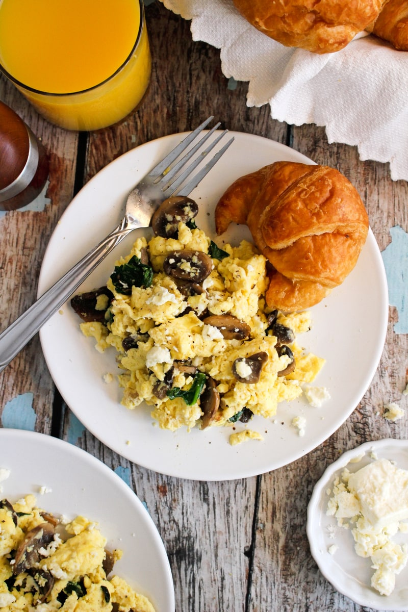 Scrambled eggs with mushrooms, spinach, and feta cheese on a white plate with a glass of orange juice to the side.