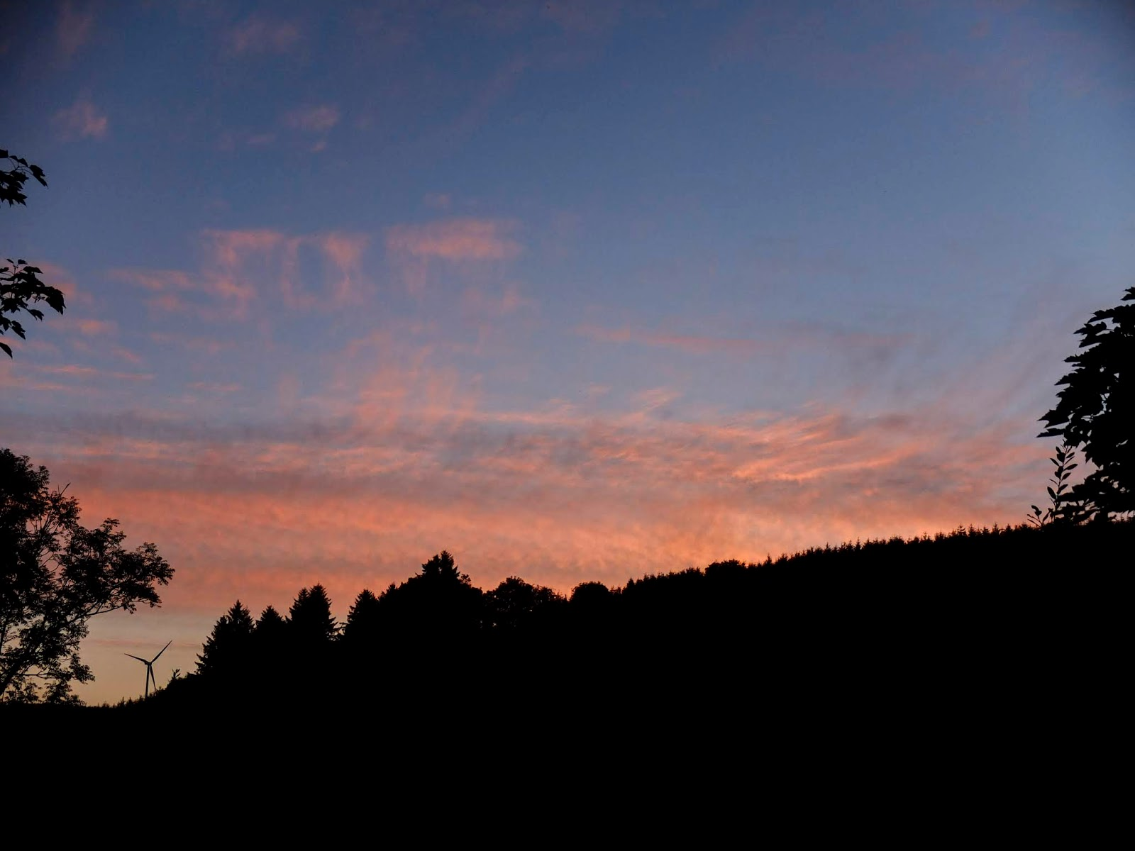 Light pink clouds on a light blue sky after sunset in the Boggeragh Mountains.