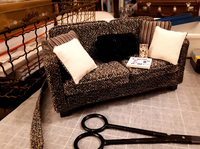 One-twelfth scale modern miniature dolls house sofa with cushions, a book and a bag of chocolate on a work surface.