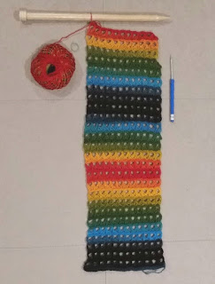 A scarf, still on the broomstick needle worked in broomstick lace and a rainbow coloured yarn. Each row introduces a new colour. Each hole is a set of broomstick loops. The ball of working/source yarn is at the top left and a blue-handled crochet hook 3 mm size is laid next to the scarf on the right hand side, pointing up.
