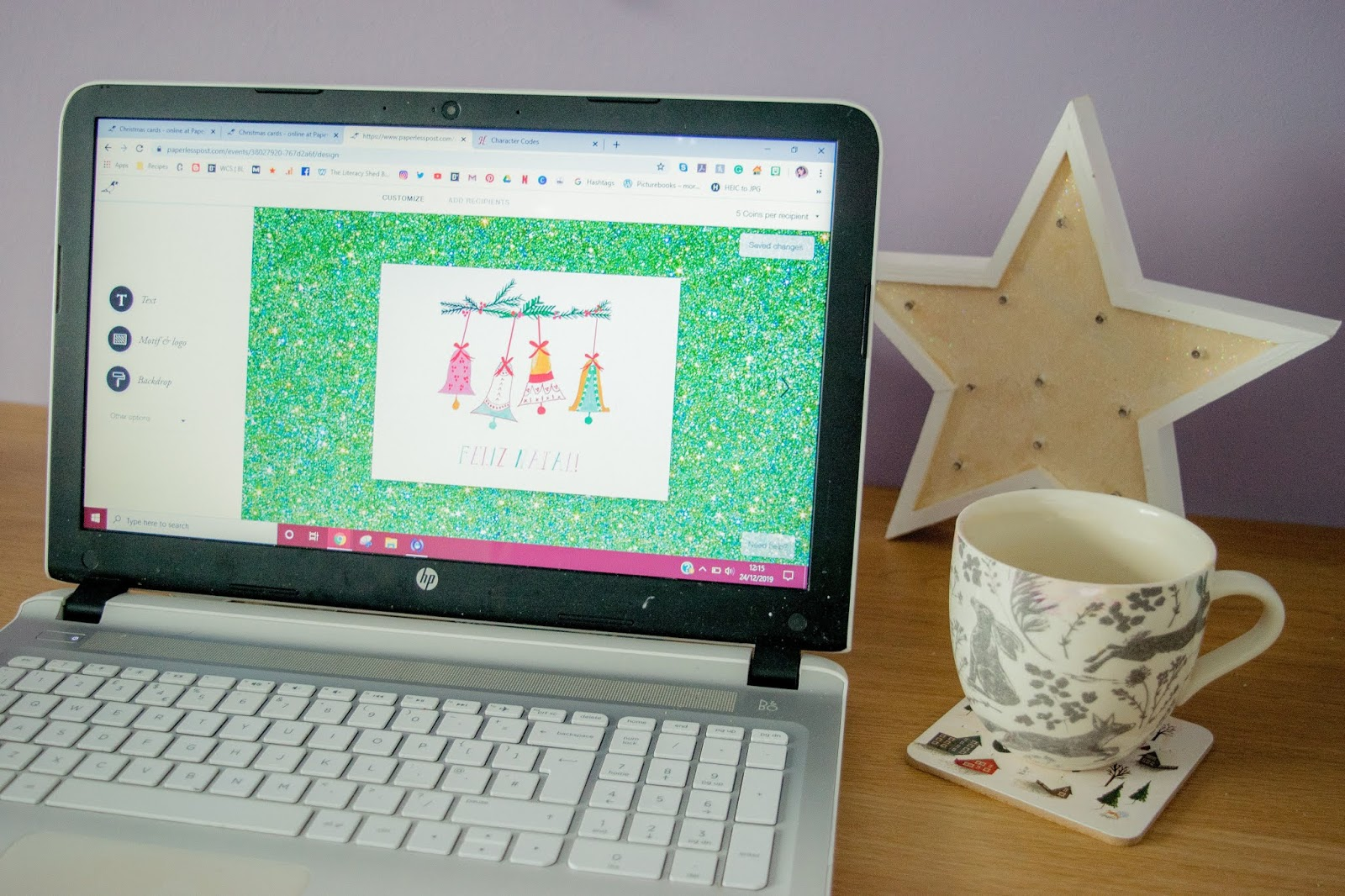 A white laptop with the Paperless Post website opened up. A white mug and a star are on the right of the laptop.