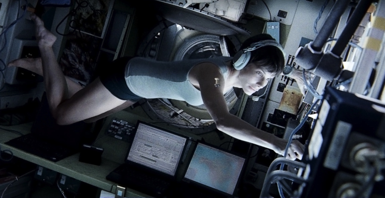 Astronaut in skivvies floating inside space station with headphones on and working at control board