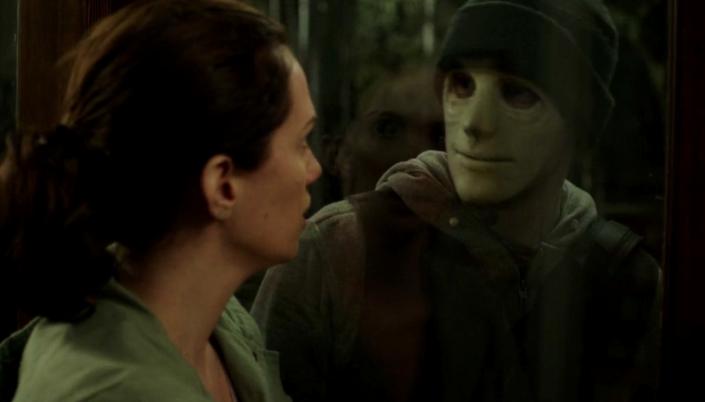 """Imagem: Filme """"Hush"""", mulher branca de cabelos presos está encarando uma janela de vidro. Do Outro lado tem um homem usando uma máscara branca, toca na cabeça e roupas de inverno. Ele tem uma expressão amena e ela expressão de pavor."""