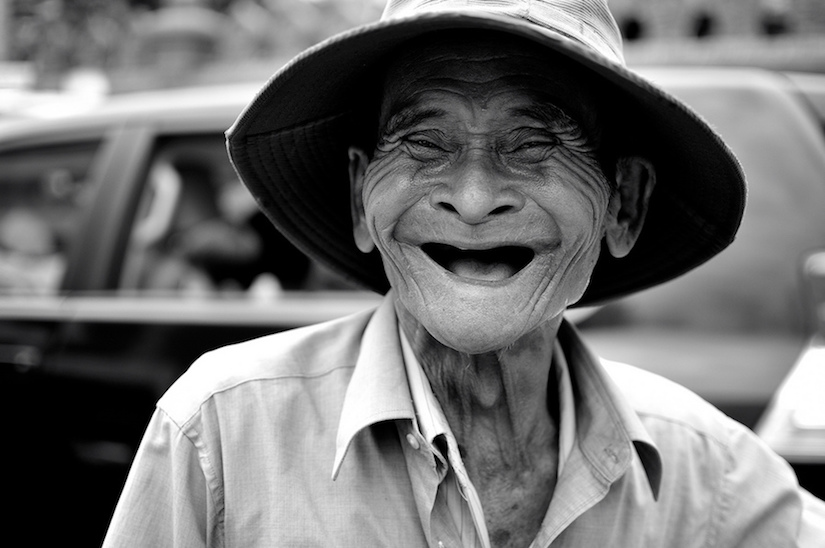 Gorgeous black and white photo of an old man without teeth laughing and wearing an Asian straw sun hat. Best April Fool. MarchMatron.com