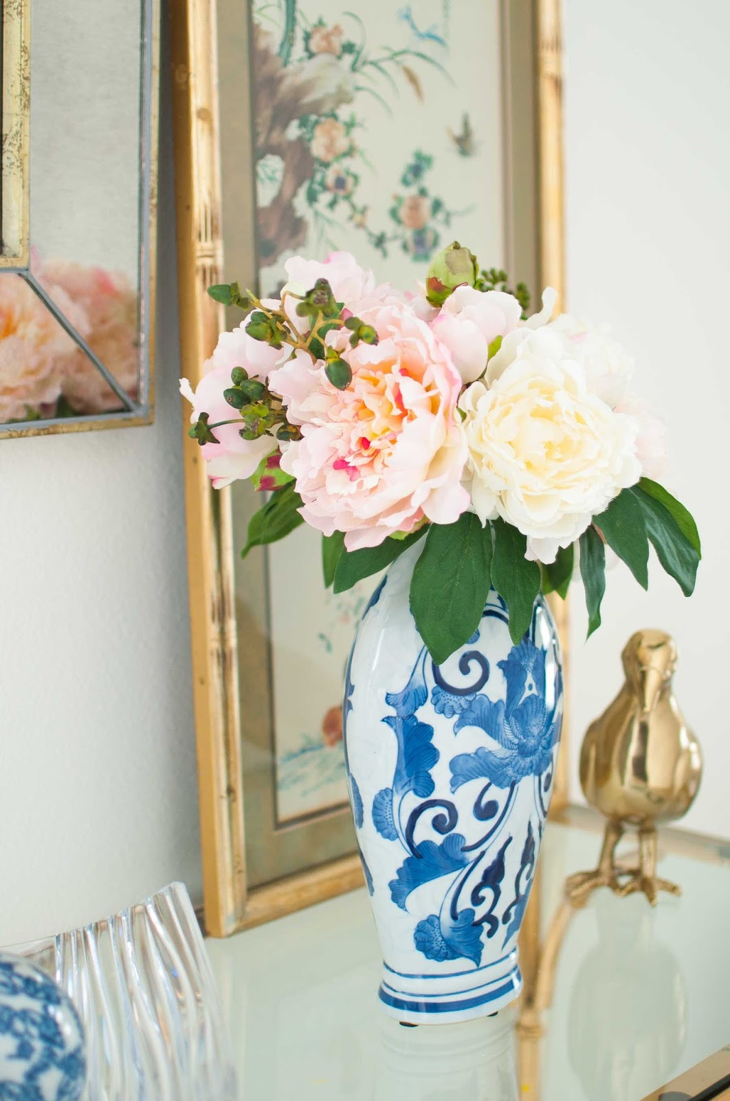 Ginger jar floral arrangement with faux florals amidst chinoiserie decor,