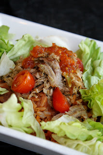 instant pot pulled pork in a white bowl on abed of butter lettuce with cherry tomato halves.