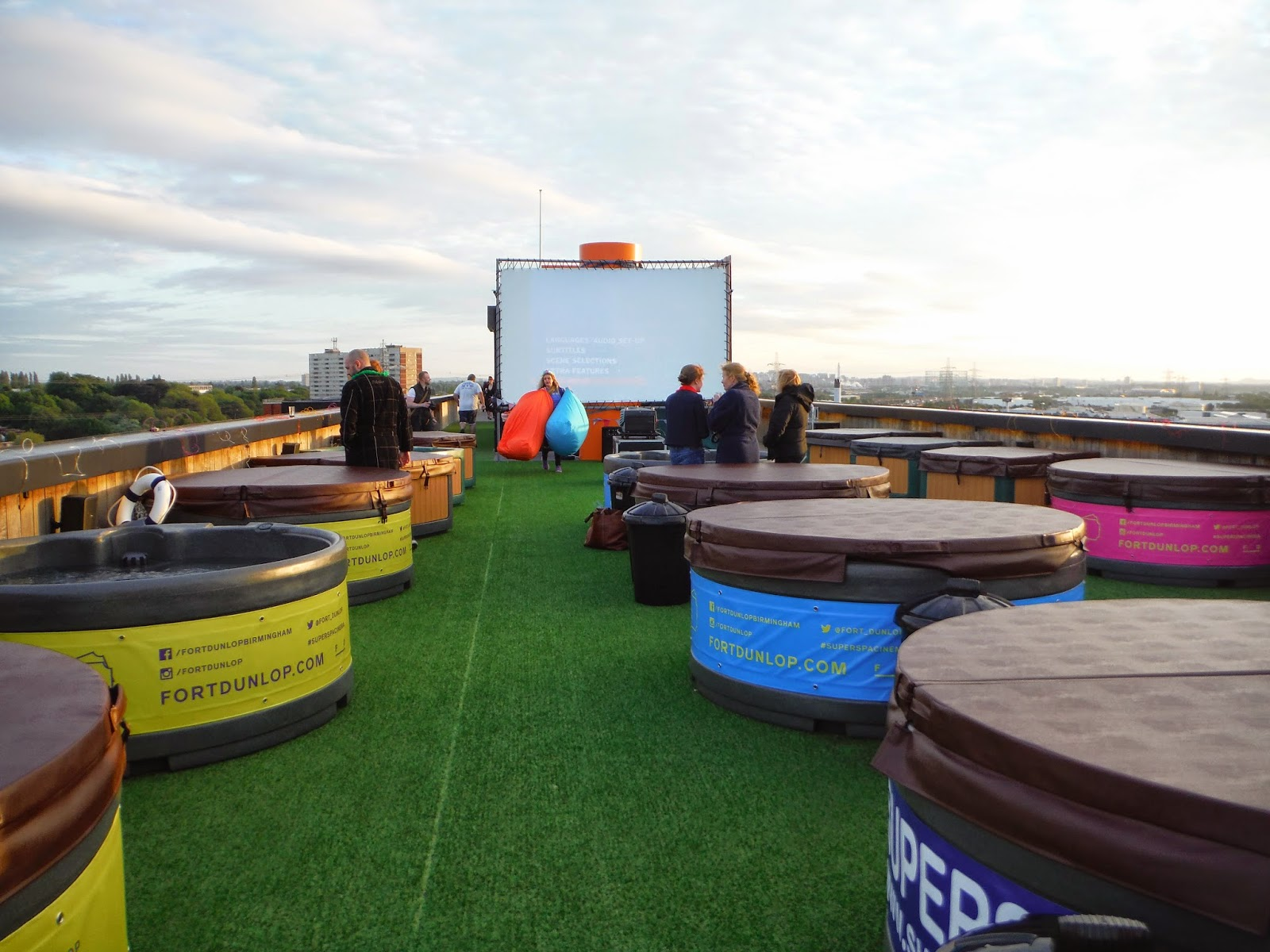 Standing at the back of the spa cinema. Multiple hot tubs can be seen in front of the outdoor cinema screen