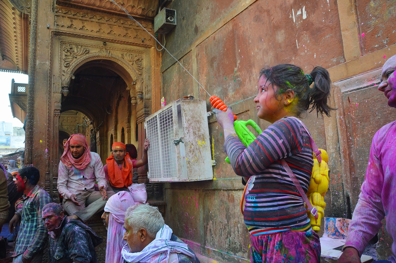 Small girl playing holi Holi Banke Bihari Temple Vrindavan 2015 colors gulal red yellow green men