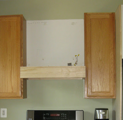 oak kitchen with space for range hood during construction