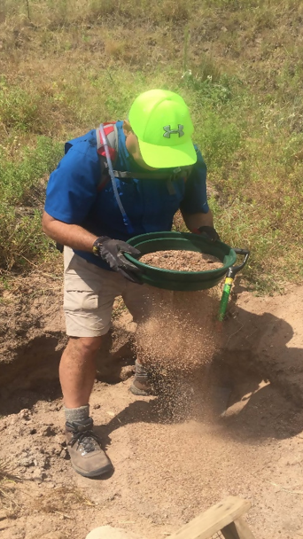 a geared-up visitor shaking dirt through a sifter