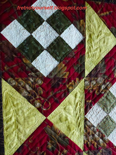 Feathers, parallel lines, and stippling are highlighted in this quilt detail.