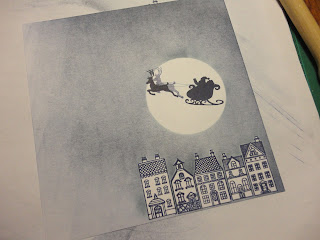 Blue houses stamped below a large moon, with Santa's sleigh
