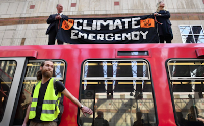 Extinction rebellion activist glues himself to a bus