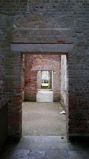 Looking through square doorways to the exit and garden beyond