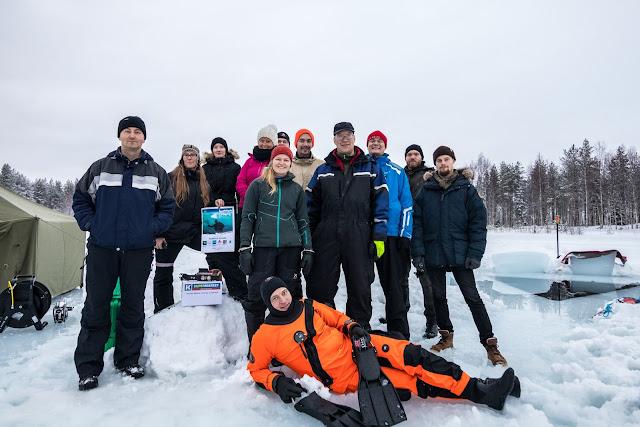 Joukko ihmisiä seisoo lumipenkalla jäähän tehdyn avannon edessä, kaikkien edessä maassa kuivapuvussa oleva sukeltaja räpylöineen