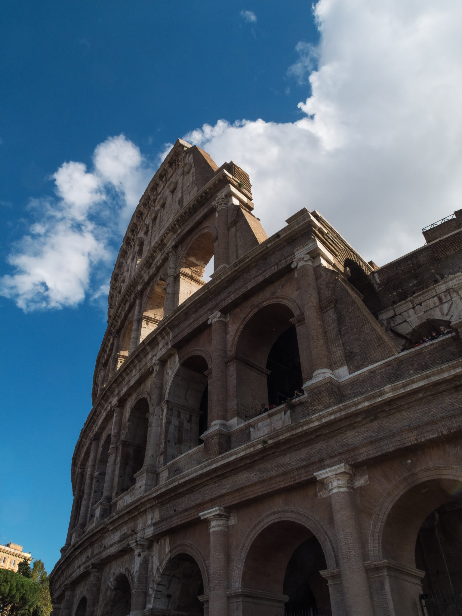 Looking up at the Colosseum and blue sky with clouds