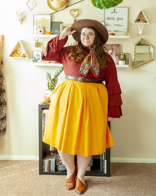 An outfit consisting of a dark brown wide brim hat, a rust red-brown tri-tiered long sleeve blouse tucked into a yellow midi skirt and cognac brown d'orsay flats.