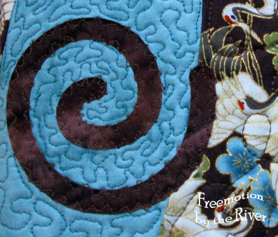 Closeup of free motion quilting on journal cover