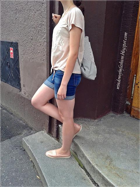 Różowa wiązana koszulka, jeansowe krótkie spodenki, espadryle, plecako-worek