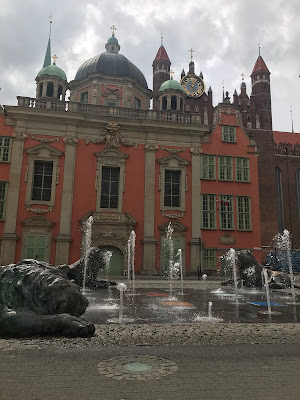 a red and green building with fountains in front of it