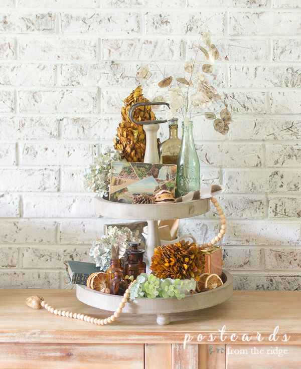 preserved boxwood, dried and natural items used as fall decor on a wooden tiered tray in front of a painted brick wall