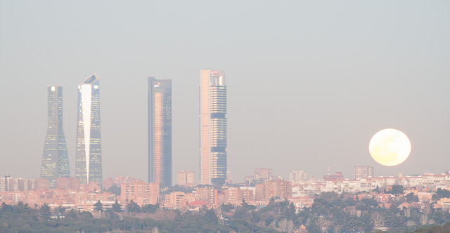 Fotografía de las 4 Torres de Madrid con la Luna llena de color naranja y muy cerca de ellas.