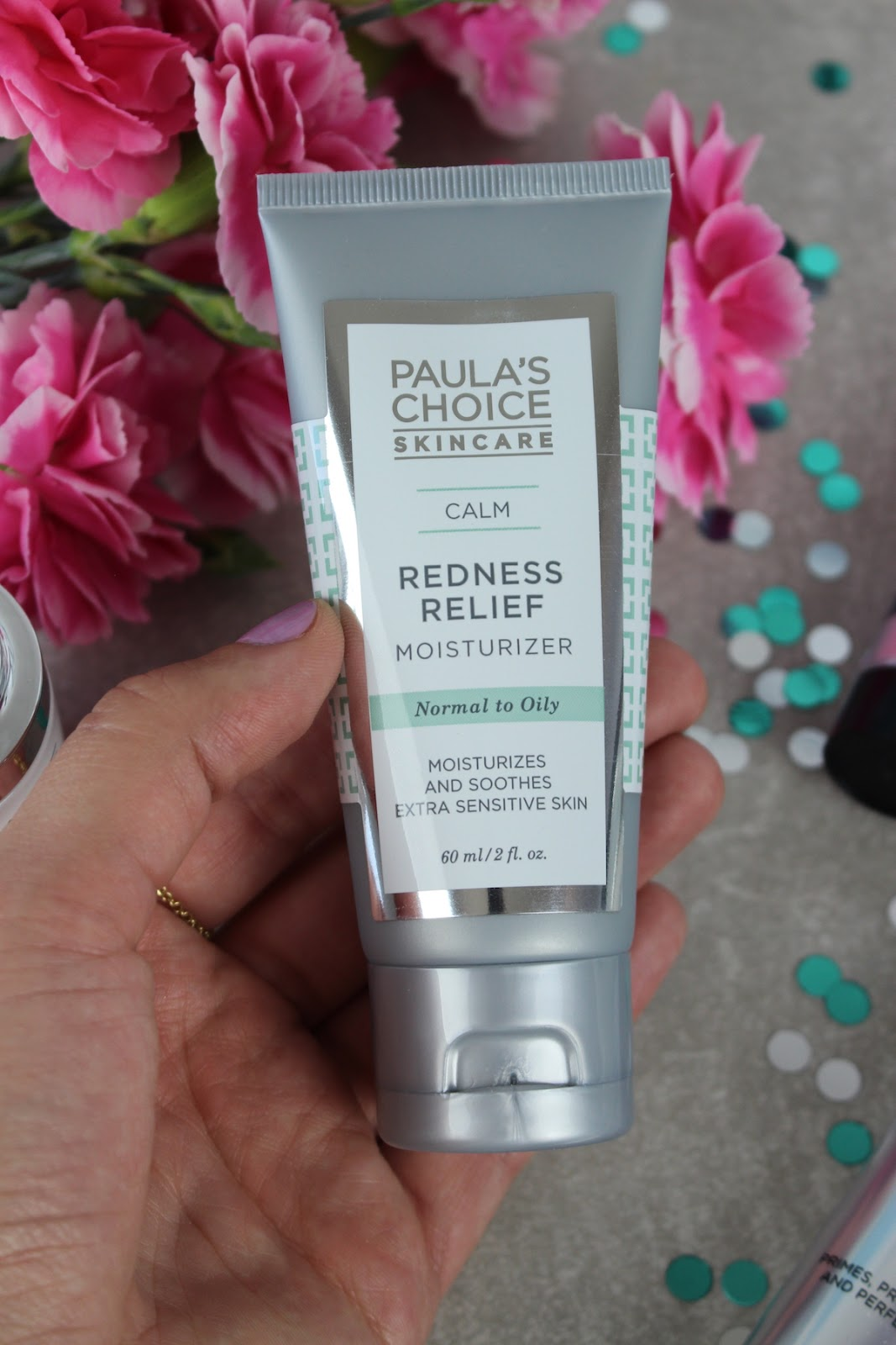This is a close up of Paula's Choice Redness Relief Moisturizer, surrounded by beautiful pink flowers.