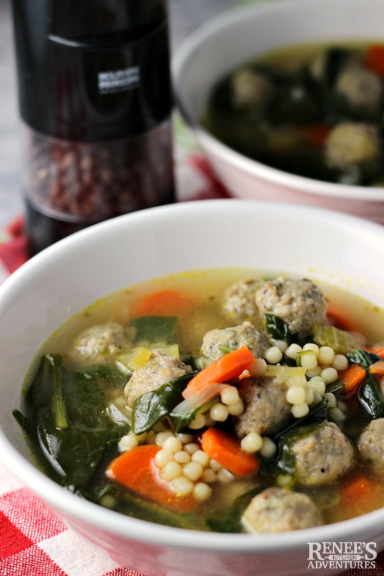 close up view of a bowl of Easy Italian Wedding Soup by Renee's Kitchen Adventures (one in the front and one behind it) with a pepper grinder to the side