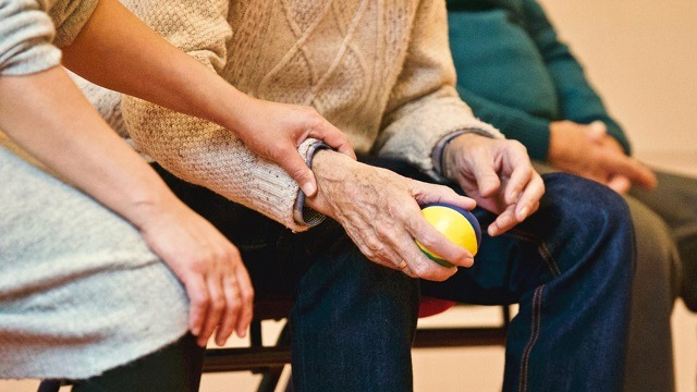 Occupational Therapist holding a senior man's hand with ball