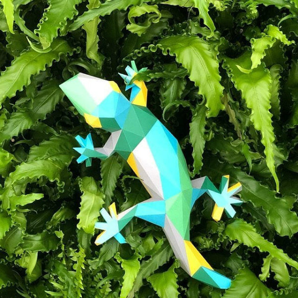 colorful folded paper gecko model placed on foliage