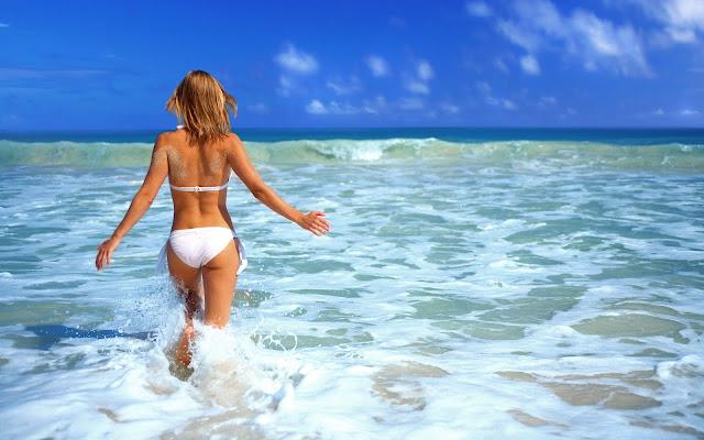 Vrouw in witte bikini loopt de zee in