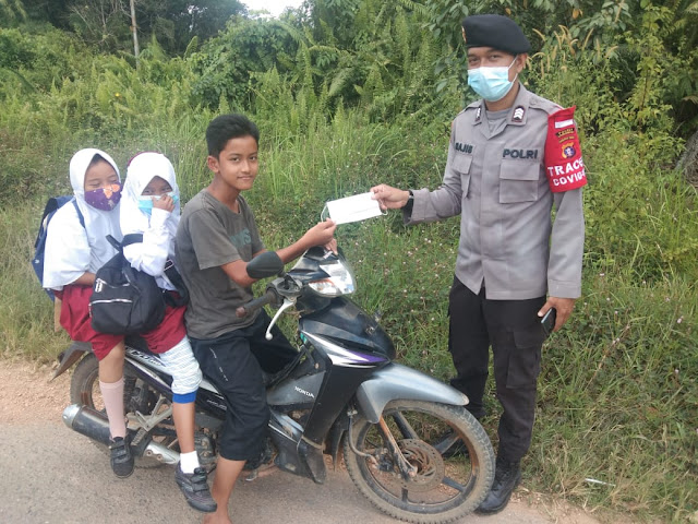 Sosialisakan bahaya covid 19, Bhabinkamtibmas Penopa bagikan masker gratis
