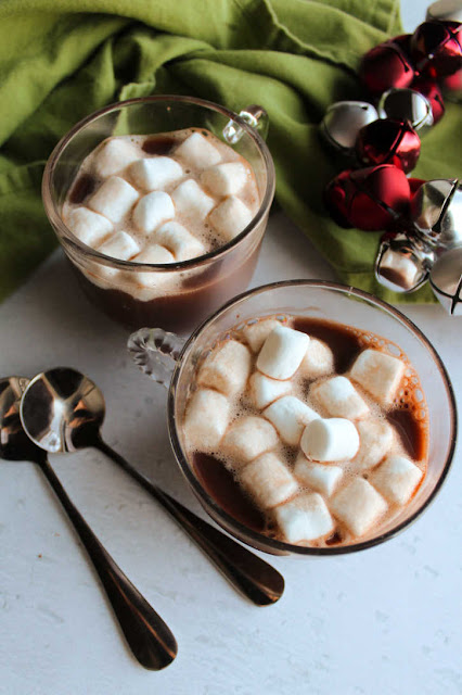 two mugs of hot chocolate and mini marshmallows ready to drink