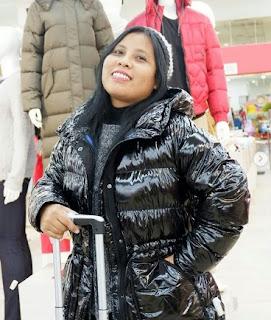 Jaket musim dingin hitam berkilat yang hangat dipadu padan dengan tutup kepala
