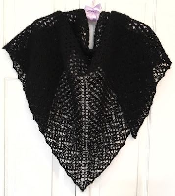 Black lacy shawl knitted with DROPS Brushed Alpaca Silk