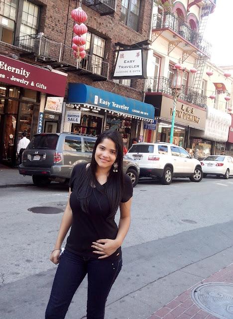 menina caelo preto, calça jeans e blusa preta em uma rua cheia de lojas