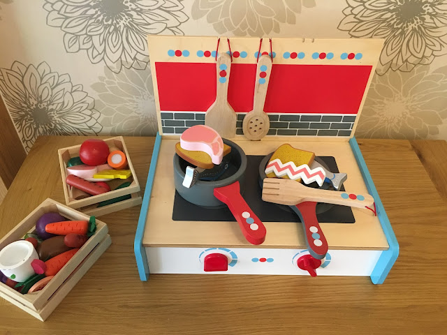 A wooden fold up cooker with pans, utensils and play food