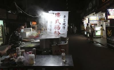 Orang-orang memakai masker wajah untuk melindungi diri dari penyebaran virus corona di pasar malam dilarang makan dan minum setelah peringatan COVID-19 naik ke level 3 di Taipei, Taiwan, Selasa, 29 Juni 2021. AP
