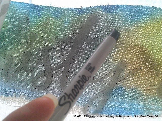 Tracing lettering onto the fabric with a permanent marker.