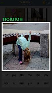 около скамейки на улице девочка делает поклон с руками  в стороны