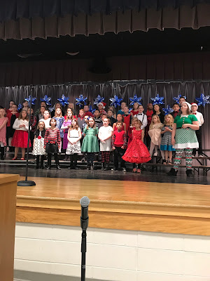 Children standing on a stage in rows side by side dressed in the spirit of Chistmas