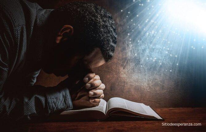 Hombre orando con Biblia