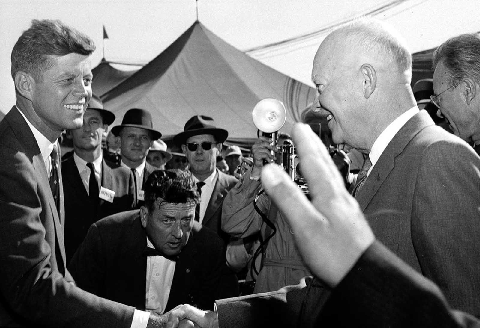 Senator John F. Kennedy greets President Dwight D. Eisenhower on his arrival for festivities at the National Corn Picking Contest near Cedar Rapids, Iowa, on October 17, 1958.