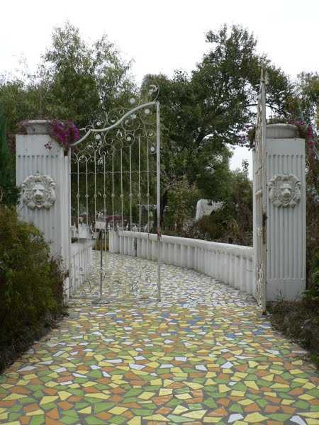 large open gate with a colorful tiled walkway through it