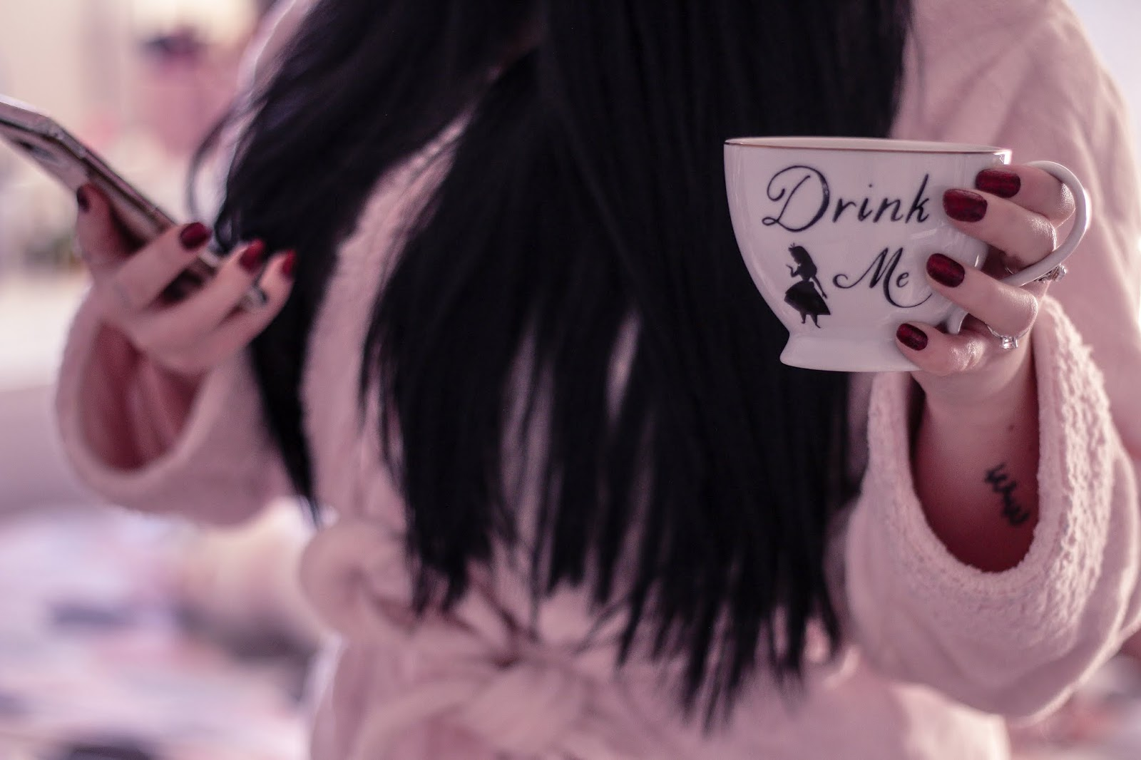 "A mid shot of myself (Jordanne Lee) standing holding a phone in right hand and white tea cup with ""Drink Me"" written on it. I am wearing a pink robe and the background is blurred"