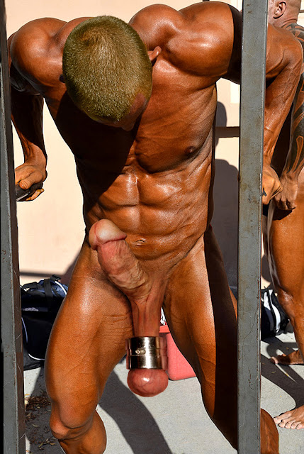 a hard young naked bodybuilder works out with a ball stretcher